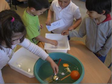 Alumnado de Infantil experimentando con objetos que flotan/no flotan